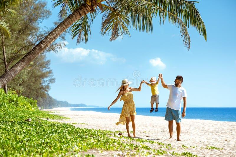 Turismo di camminata della spiaggia della famiglia felice immagini stock libere da diritti