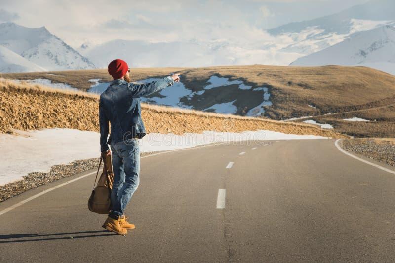 Turismo e conceito dos povos - moderno à moda que anda ao longo da estrada secundária fora e que aponta o dedo a algo fotografia de stock