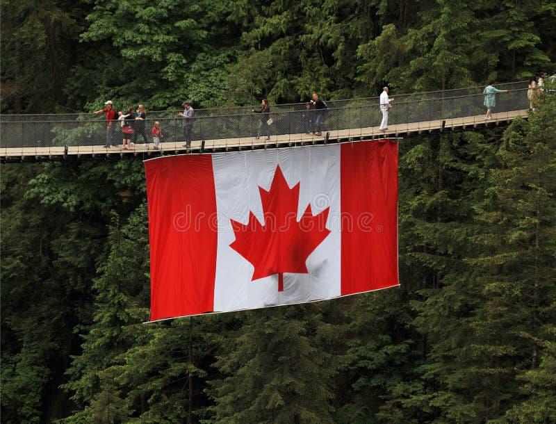Turismo en Canadá: Puente colgante de Capilano con la bandera canadiense foto de archivo libre de regalías