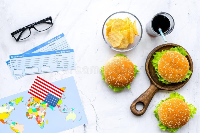Turismo gastronómico con la bandera americana, pasaporte, boletos, mapa, hamburguesas, microprocesadores, bebida en la opinión su imagen de archivo