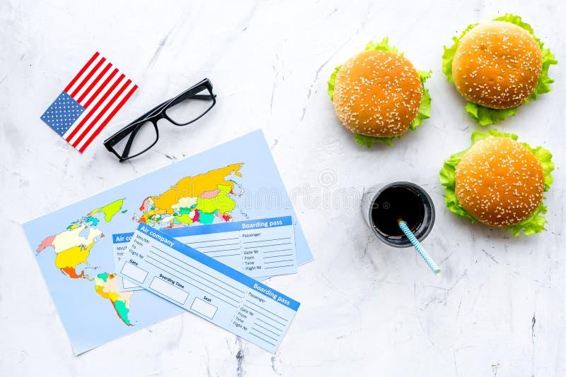 Turismo gastronómico con la bandera americana, pasaporte, boletos, mapa, hamburguesas, microprocesadores, bebida en la opinión su fotografía de archivo
