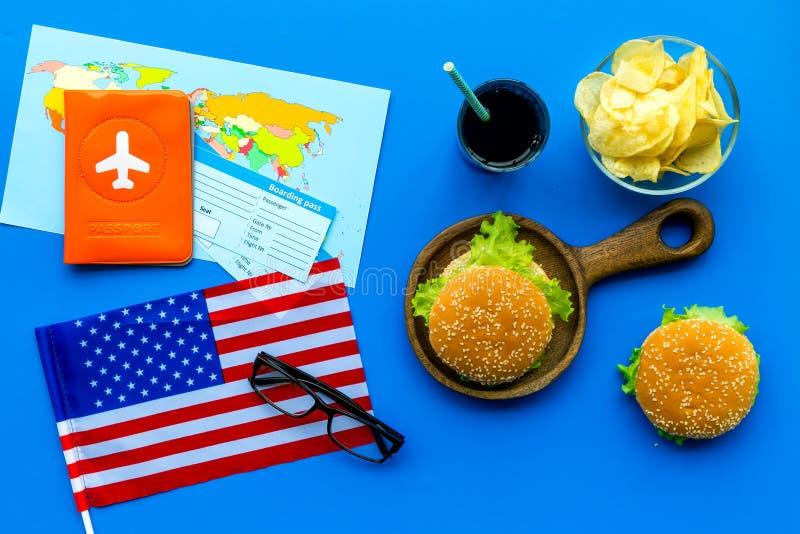 Turismo gastronómico con la bandera americana, pasaporte, boletos, mapa, hamburguesas, microprocesadores, bebida en la opinión su imagen de archivo libre de regalías