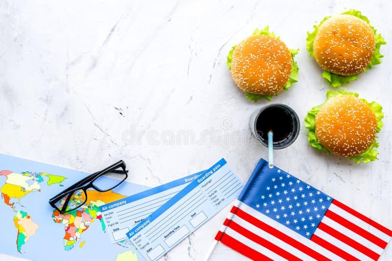 Turismo gastronómico con la bandera americana, pasaporte, boletos, mapa, hamburguesas, microprocesadores, bebida en la opinión su fotografía de archivo libre de regalías