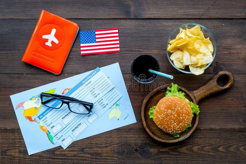 Turismo gastronómico con la bandera americana, pasaporte, boletos, mapa, hamburguesas, microprocesadores, bebida en la opinión su fotos de archivo