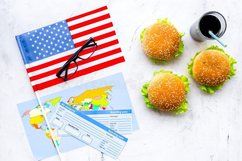 Turismo gastronómico con la bandera americana, pasaporte, boletos, mapa, hamburguesas, microprocesadores, coque en la opinión sup foto de archivo libre de regalías