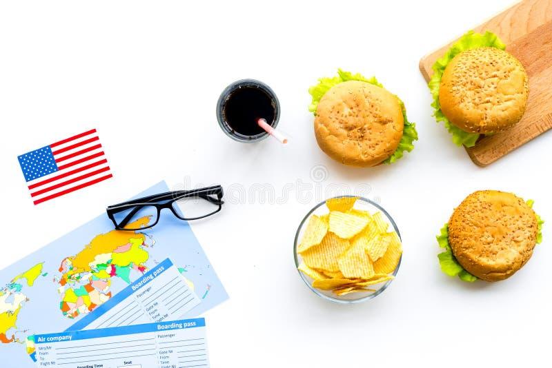 Turismo gastronómico con la bandera americana, pasaporte, boletos, mapa, hamburguesas, microprocesadores en la opinión superior d fotos de archivo