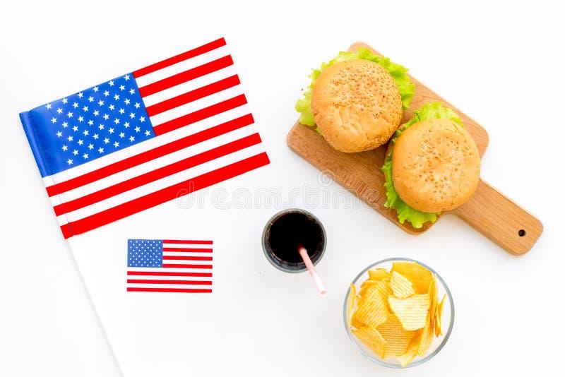 Turismo gastronómico con la bandera americana y las hamburguesas, microprocesadores, coque en la opinión superior del fondo blanc fotos de archivo