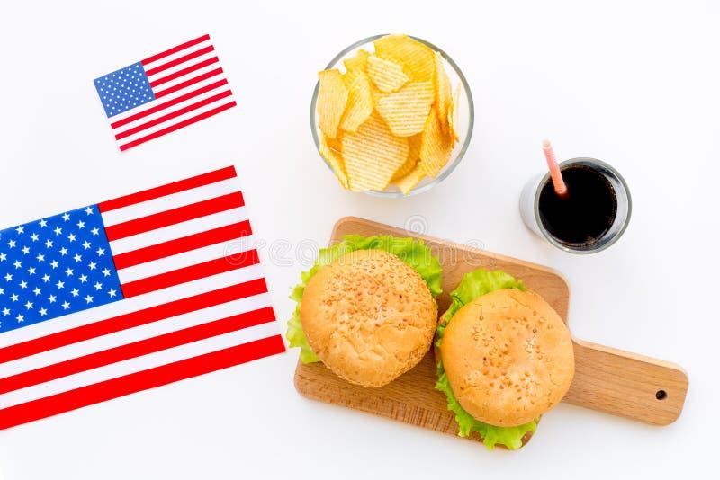 Turismo gastronómico con la bandera americana y las hamburguesas, microprocesadores, coque en la opinión superior del fondo blanc imágenes de archivo libres de regalías