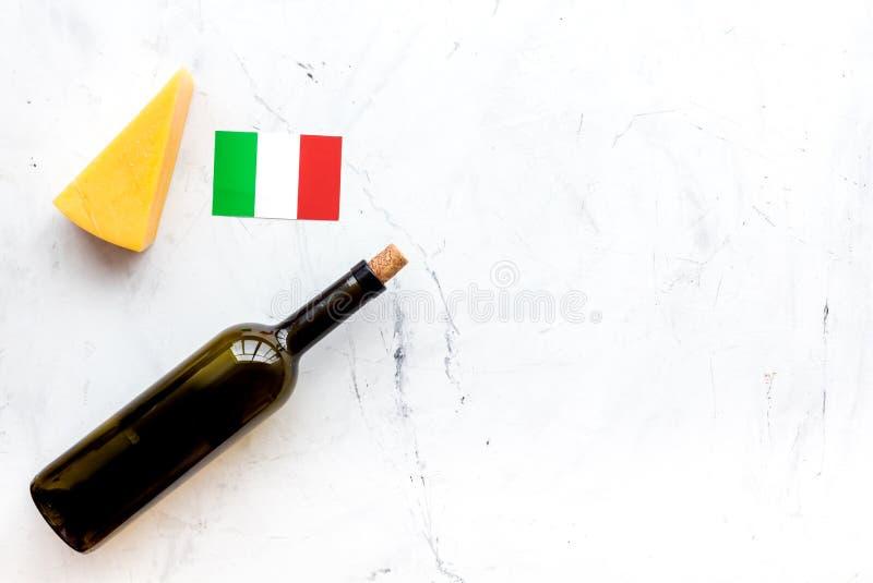 Turismo gastronómico Símbolos italianos de la comida Bandera, parmesano del queso y botella italianos de vino tinto en el fondo b imagenes de archivo