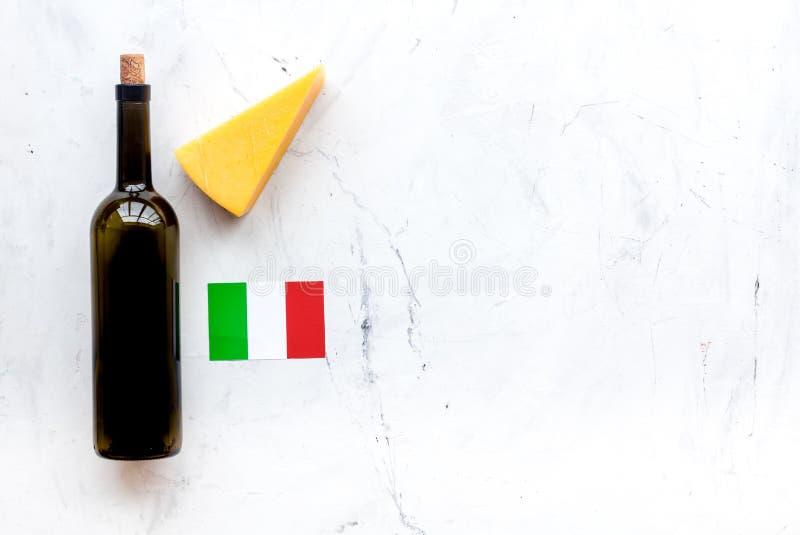 Turismo gastronómico Símbolos italianos de la comida Bandera, parmesano del queso y botella italianos de vino tinto en el fondo b foto de archivo libre de regalías