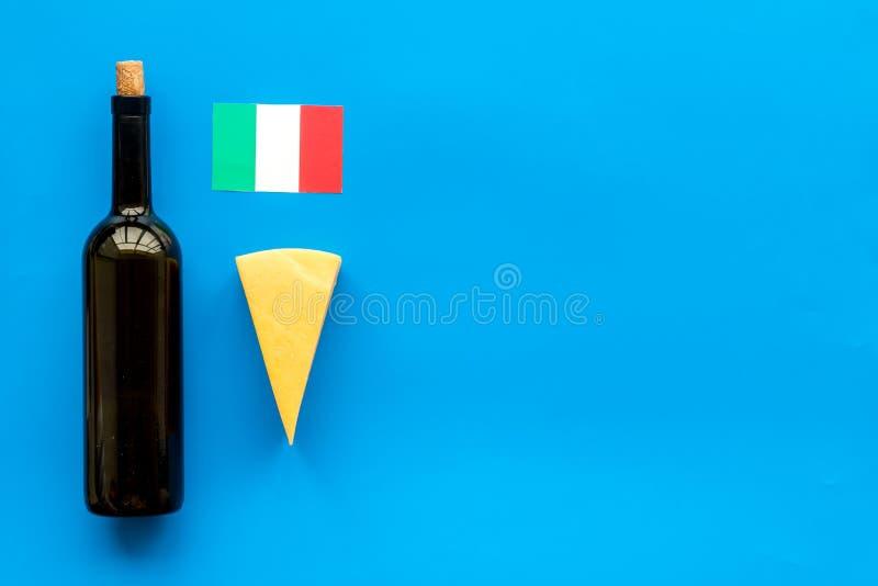 Turismo gastronómico Símbolos italianos de la comida Bandera, parmesano del queso y botella italianos de vino tinto en el top azu fotografía de archivo libre de regalías