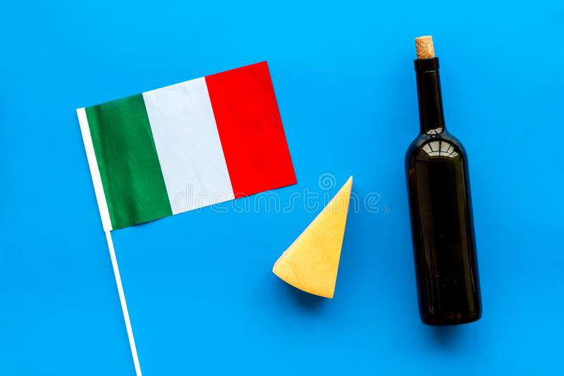 Turismo gastronómico Símbolos italianos de la comida Bandera, parmesano del queso y botella italianos de vino tinto en el top azu fotos de archivo