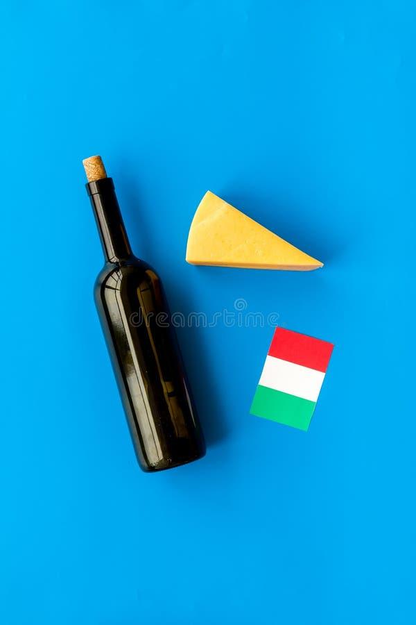 Turismo gastronómico Símbolos italianos de la comida Bandera, parmesano del queso y botella italianos de vino tinto en el top azu fotografía de archivo