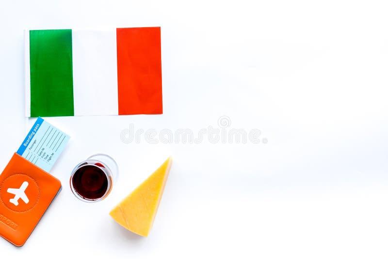 Turismo gastronómico Símbolos italianos de la comida Pasaporte y boletos cerca de la bandera italiana, vidrio de vino tinto, parm foto de archivo