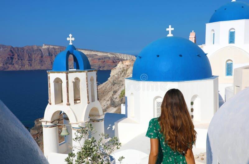Turismo na Grécia Vista de trás de uma turista viajante visitando a famosa vila branca com cúpulas azuis de Oia, Santorini imagem de stock royalty free