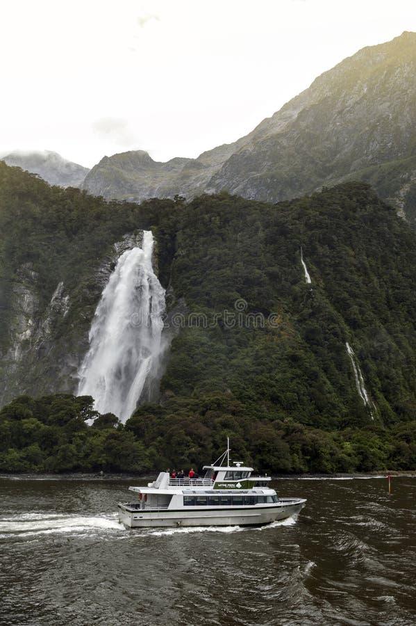 Turist- övergående dam Bowen Falls, Milford Sound, Nya Zeeland för kryssningskepp royaltyfri fotografi