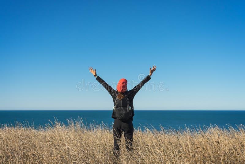 Turist- anseende för kvinna på äng med havsikt royaltyfri foto