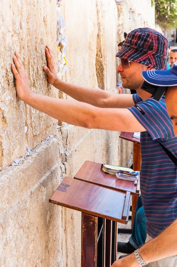 Turist- anseende för ung man som tänker vad för att fråga från gud och trycker på heliga stenar av den västra väggen, som är rest arkivbilder