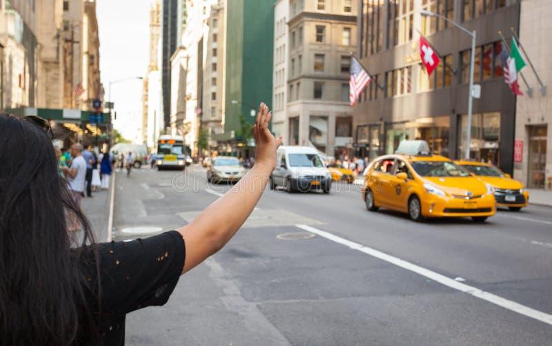 Turist- appell en gul taxi i Manhattan med typisk gest royaltyfria bilder