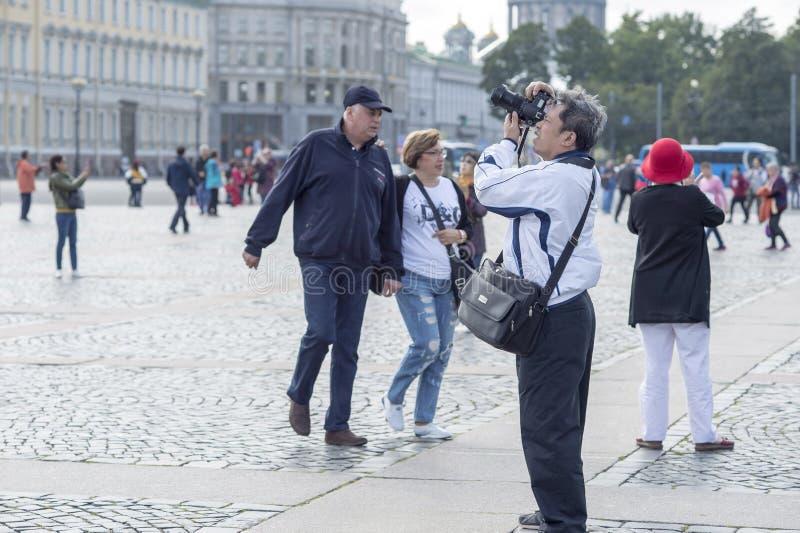 Turist- asiatiska utseendemässiga fotografier för man på kameradragningar på slottfyrkanten av St Petersburg, Ryssland, September arkivbild