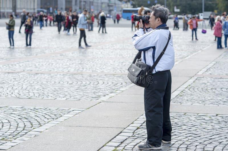 Turist- asiatiska utseendemässiga fotografier för man på kameradragningar på slottfyrkanten av St Petersburg, Ryssland, September arkivfoto