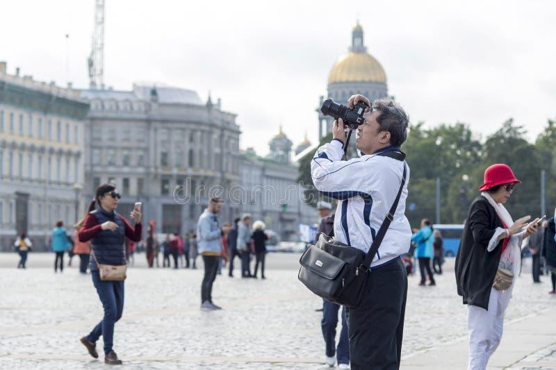 Turist- asiatiska utseendemässiga fotografier för man på kameradragningar på slottfyrkanten av St Petersburg, Ryssland, September arkivbilder