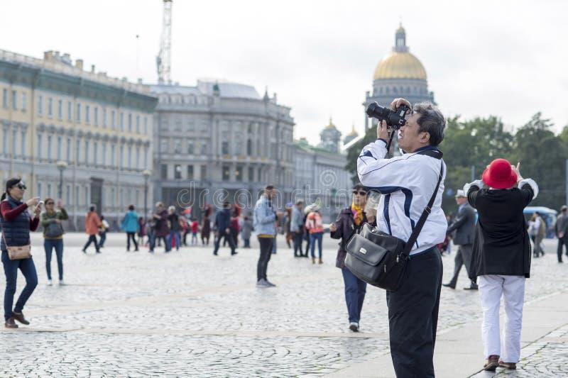 Turist- asiatiska utseendemässiga fotografier för man på kameradragningar på slottfyrkanten av St Petersburg, Ryssland, September royaltyfri foto