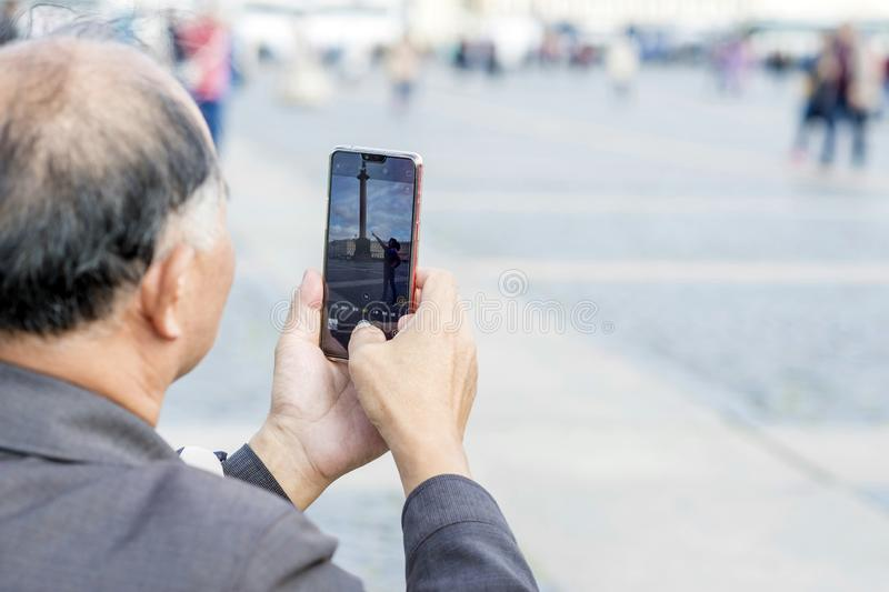 Turist- asiatiska utseendemässiga fotografier för man på smartphonekvinnan som poserar på slottfyrkanten St Petersburg, Ryssland, royaltyfri bild