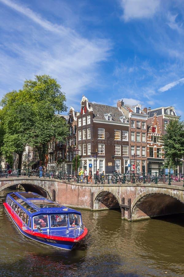 Turist- cruiseboat i kanalerna av historiska Amsterdam royaltyfri foto
