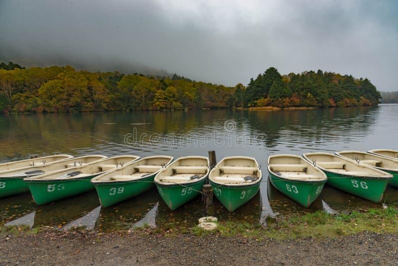 Turist eller fiskebåtar som svävar på en sjö med gråa moln och träd som ändrar färg i höst royaltyfri bild
