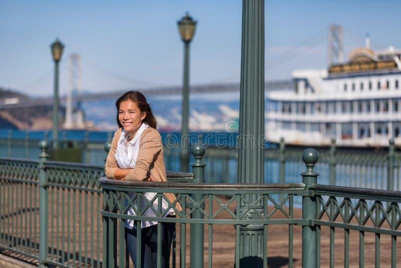 Turist för flicka för lopp för San Francisco kryssningsemester på pir av port Asiatisk kvinna som ser sikt av hamnen på marina av royaltyfri fotografi