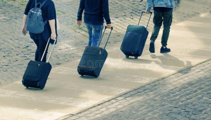 Turist för tre handelsresande som bär deras bagage på en fot- gångbana Den bästa sikten och tömmer kopieringsutrymme arkivfoto