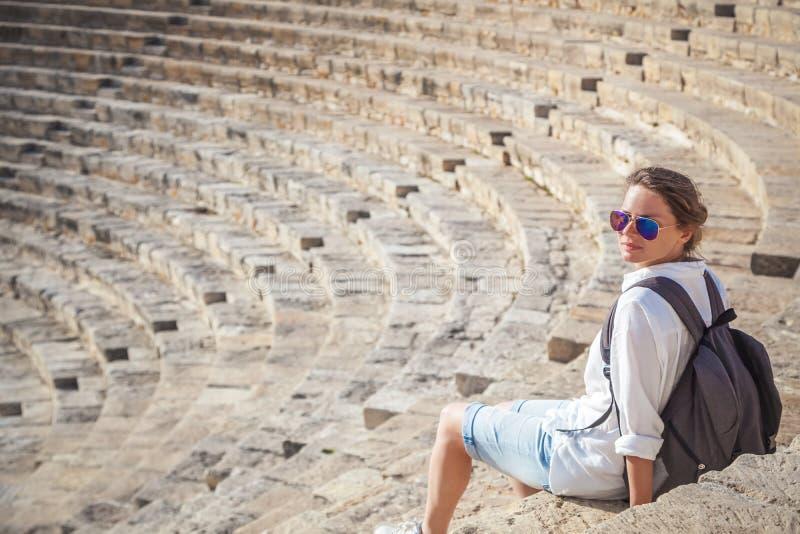 Turist för ung kvinna med en ryggsäck på bakgrunden av sten royaltyfri fotografi