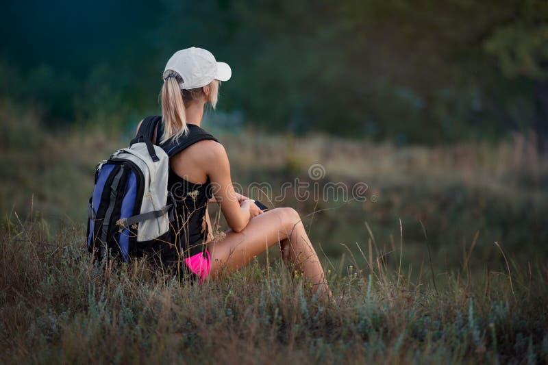 Turist för ung kvinna med ryggsäcken som vilar på en äng, i et royaltyfri foto