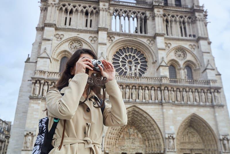 Turist för ung kvinna som fotograferar med kameran som framme står av den berömda Notre Dame domkyrkan i Paris arkivbilder