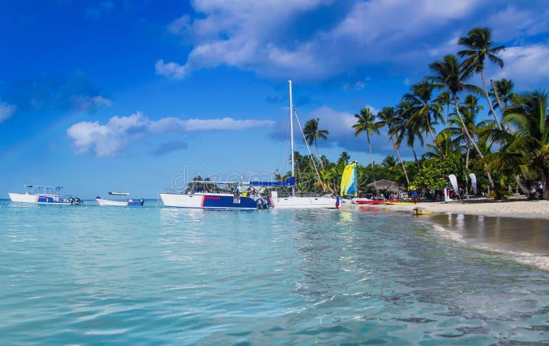 Turist- fartyg av kusten av det karibiska havet Stranden av ön av Saone i molnigt väder Regnbåge över ön royaltyfri foto