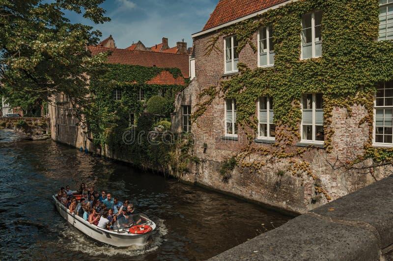 Turist- fartyg på kanal- och tegelstenbyggnad på Bruges royaltyfri fotografi