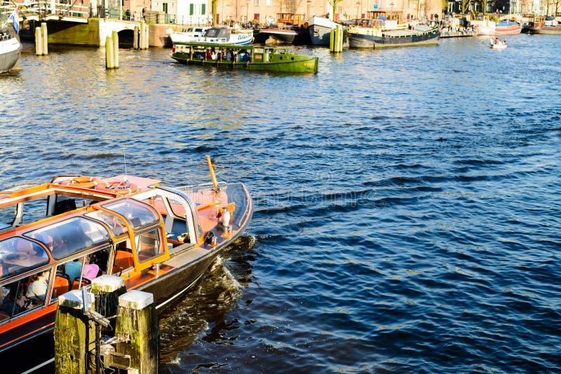 Turist- fartyg på kanalen under utfärd i Amsterdam, net arkivbild