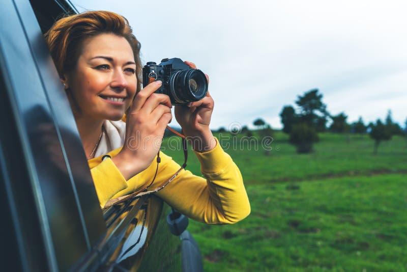 Turist- flicka för leende i ett öppet fönster av en automatiskbil som tar på fotografiklicken på retro tappningfotokamera, fotogr royaltyfri fotografi