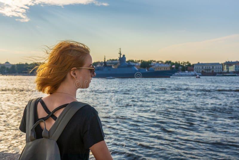 Turist- flicka för rödhårig mantween på den Neva flodinvallningen som ser krigsskepp och den arkitektoniska helheten i sommarafto arkivbild