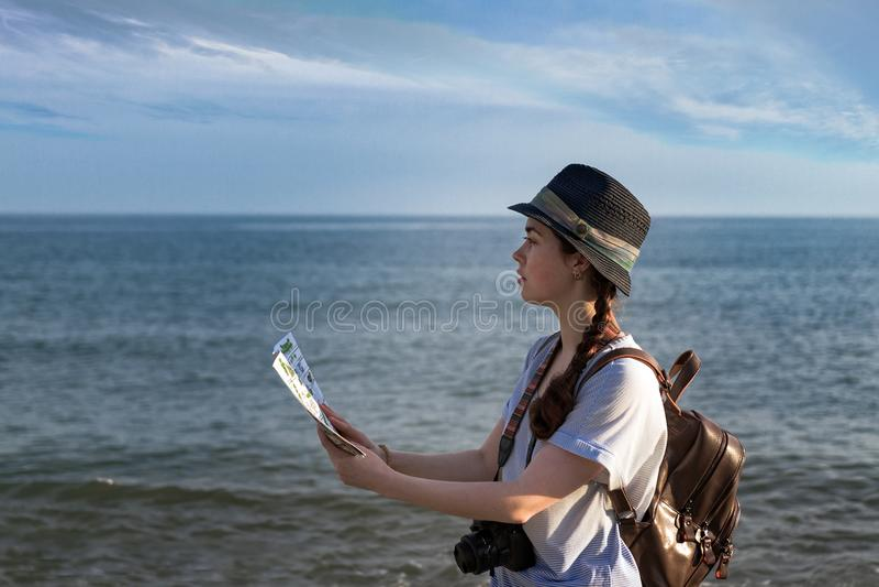 Turist- flicka, med en ryggsäck, en kamera och en hatt som ser översikten royaltyfria bilder