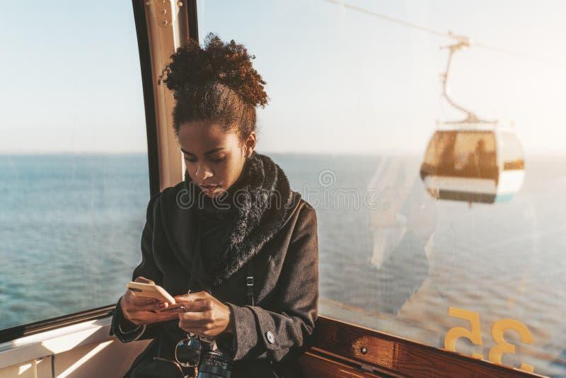 Turist- flicka som använder telefonen i cableway royaltyfria bilder