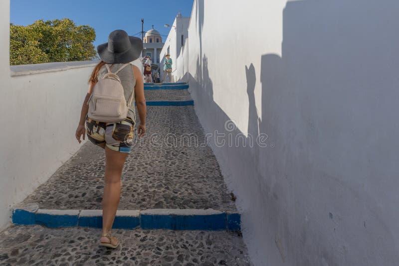 Turist- flicka som går i gatorna av Fira royaltyfria foton