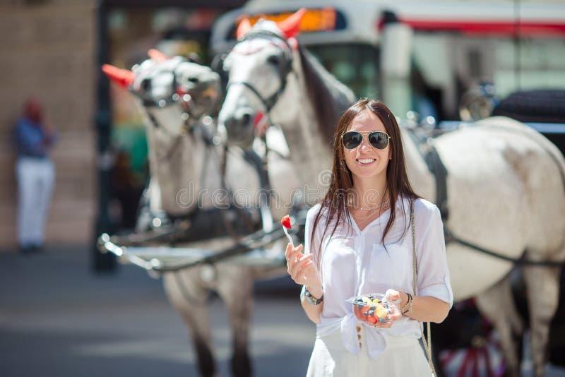 Turist- flicka som tycker om en promenad till och med Wien och ser de härliga hästarna i vagnen royaltyfri bild
