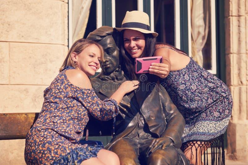 Turist- flickor som tar Selfie nära statyn i den Habana Kuban arkivfoto