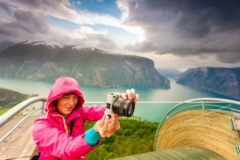 Turist- fotograf med kameran på Stegastein utkik, Norge arkivfoton