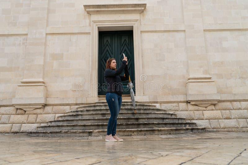 Turist- fotografier för ung kvinna på en gammal stad arkivbilder