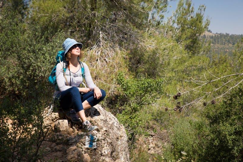 Turist- fotvandraresammanträde för kvinna som vilar stenen som fotvandrar skoglandskap arkivbild