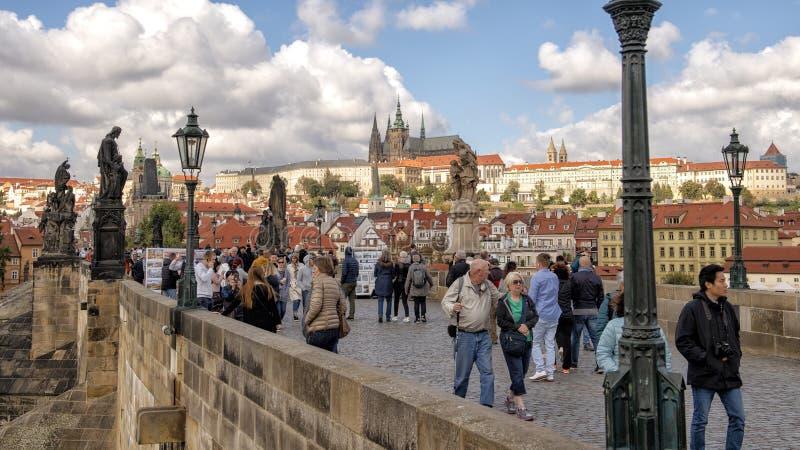Turist- fyllda Charles Bridge med det är berömda skulpturer, med den Prague slotten i bakgrunden, Prague, Tjeckien royaltyfri fotografi