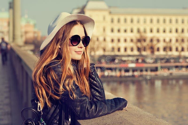 Turist- gladlynt flicka för ung nätt hipster som poserar på gatan på den soliga dagen och reser runt om europeisk stad royaltyfria foton